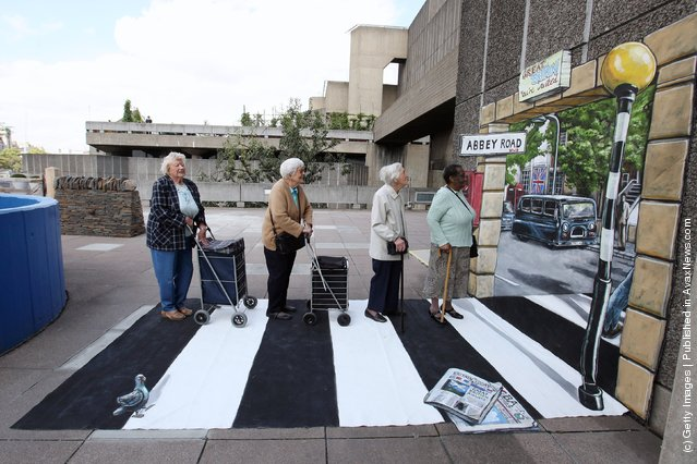 Four elderly women recreate a pose from the front cover of the Beatles Abbey Road album on artwork outside the Hayward Gallery