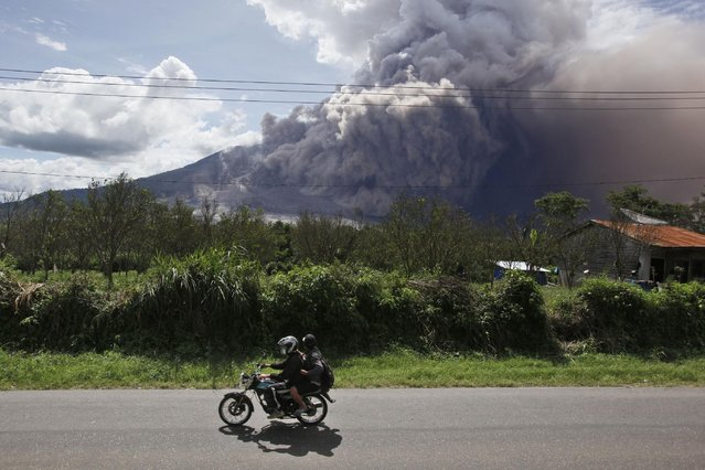 Motorists ride past by as Mount Sinabung erupts, in Beganding, North Sumatra, Indonesia, Saturday, June 13, 2015. The volcano, which was put on it highest alert level last week, has sporadically erupted since 2010 after being dormant for 400 years. (AP Photo/Binsar Bakkara)