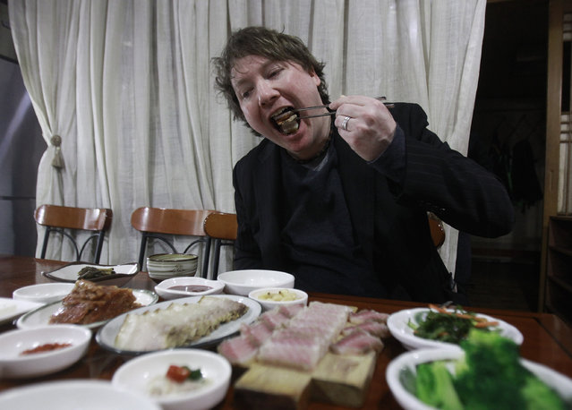 In this March 12, 2014 photo, Joe McPherson, operator of a Korean food blog Zen Kimchi, eats a Samhap, with skate, kimchi, and boiled pork all together, at a seafood store in Seoul, South Korea. (Photo by Ahn Young-joon/AP Photo)