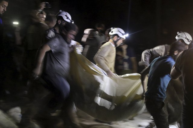 Civil defence members carry a casualty after an airstrike at a field hospital in the rebel held area of al-Sukari district of Aleppo, Syria April 27, 2016. (Photo by Abdalrhman Ismail/Reuters)
