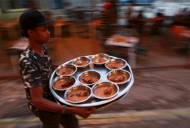 A volunteer carries food to tables set up by a charity as people wait to eat their Iftar (breaking of fast) meal during the holy fasting month of Ramadan in Benghazi, Libya  June 27, 2015. (Photo by Esam Omran Al-Fetori/Reuters)
