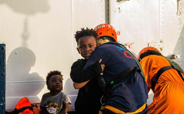 "Handout picture taken on July 31, 2019 by German migrant rescue NGO Sea-Eye, shows children rescued off an overloaded rubber boat spotted in international waters off the Libyan coast, being brought on their vessel ""Alan Kurdi"". The German aid organization Sea-Eye has rescued 40 people from an overcrowded rubber dinghy in the Mediterranean. The crew of the rescue ship ""Alan Kurdi"" discovered the migrants early morning on July 31, 2019 in international waters and took them on board, Sea-Eye said. The ""Alan Kurdi"" is now heading for the Italian Mediterranean island of Lampedusa. (Photo by Pavel Vitko/AFP Photo)"