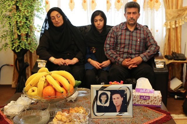 Samereh Alinejad (L), Abdolghani Hosseinzadeh (R) and their daughter sit on a sofa in front of a picture of their son Abdolah Hosseinzadeh who was killed by a fellow Iranian, Balal, in a street fight with a knife in 2007, after they spared the life of their son's convicted murderer during his execution ceremony in the northern city of Nowshahr on April 15, 2014. Alinejad spared the life of her son's convicted murderer with an emotional slap in the face as he awaited execution with the noose around his neck, a newspaper resported. (Photo by Araash Khamooshi/AFP Photo/ISNA)