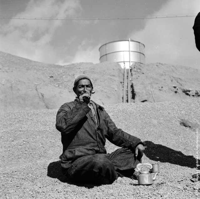 1954:  An Iranian oil worker in an arid landscape, an oil tank in the distance, sits enjoying the labourer's staple diet of bread and tea