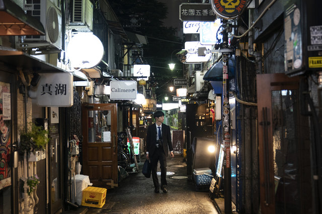 A man strolls through a narrow alleyway clustered with tiny bars and restaurants at the Golden Gai in the Shinjuku district of Tokyo, July 17, 2019. (Photo by Jae C. Hong/AP Photo)
