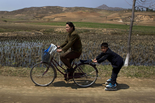 A North Korean boy on rollerblades is pulled by a woman on a bicycle on Wednesday, April 24, 2013, on a road south of Kaesong, North Korea and north of the demilitarized zone which separates the two Koreas. (Photo by David Guttenfelder/AP Photo)