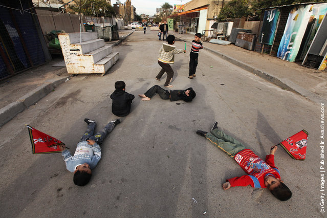 Children play while re-enacting the Battle of Karbala outside Seid Idrees mosque on the day before the festival Ashura in Baghdad, Iraq