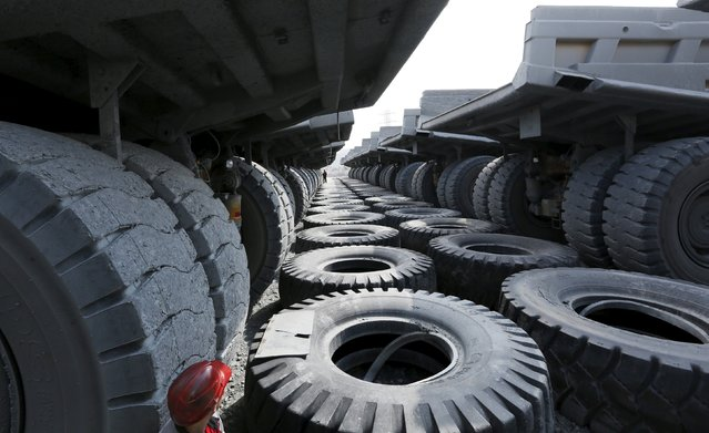 Employees walk along lines of parked Caterpillar 136 tons load-carrying capacity dump trucks before the beginning of the working shift at the Vostochny opencast of the Olimpiada gold operation, owned by Polyus Gold International company, in Krasnoyarsk region, Eastern Siberia, Russia, June 30, 2015. (Photo by Ilya Naymushin/Reuters)