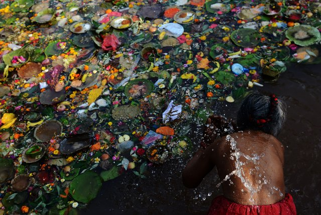 A Nepalese Hindu devotee takes a holy bath as they mark the Mother's Day Festival at Matathirtha on the outskirts of Kathmandu on May 6, 2016. Nepalese Hindu devotees come from across the country to bathe, offer prayers and leave offerings at the Matathirtha Temple during the event, which honours mothers who have passed away. (Photo by Prakash Mathema/AFP Photo)