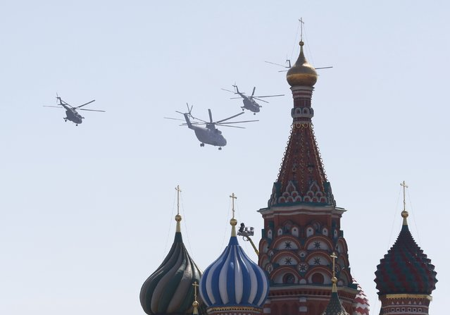 A Russian Mi-26 heavy transport helicopter and Mi-8 military helicopters fly in formation during the Victory Day parade, marking the 71st anniversary of the victory over Nazi Germany in World War Two, above St. Basil's Cathedral at Red Square in Moscow, Russia, May 9, 2016. (Photo by Grigory Dukor/Reuters)