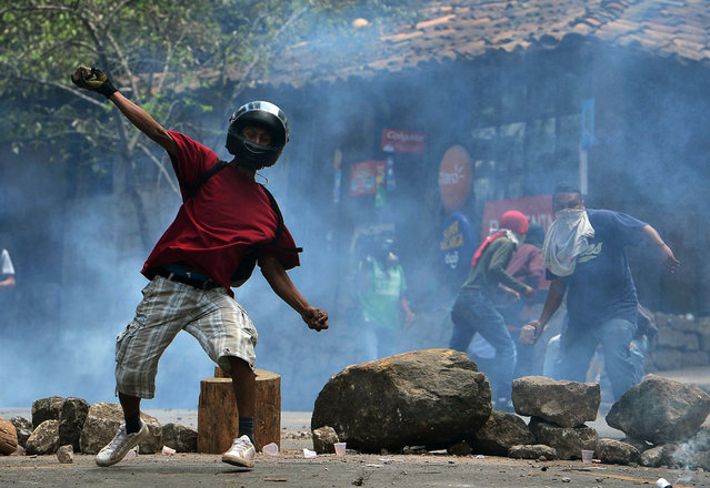 Residents of El Hatillo throw stones at riot police during a protest against the construction of a housing project in the outskirts of Tegucigalpa, on September 17, 2019. The residents demand the cancellation of the project arguing that it threatens to leave the Honduran capital without drinking water. Honduras declared a state of emergency on September 5 due to severe drought that is affecting the main cities of the country. (Photo by Orlando Sierra/AFP Photo)