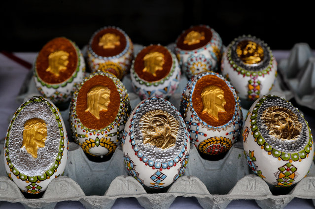 In this Thursday, April 13, 2017, picture Easter eggs decorated with religious themes by artisan Nicu Poenariu are on sale at a fair in Bucharest, Romania. (Photo by Vadim Ghirda/AP Photo)