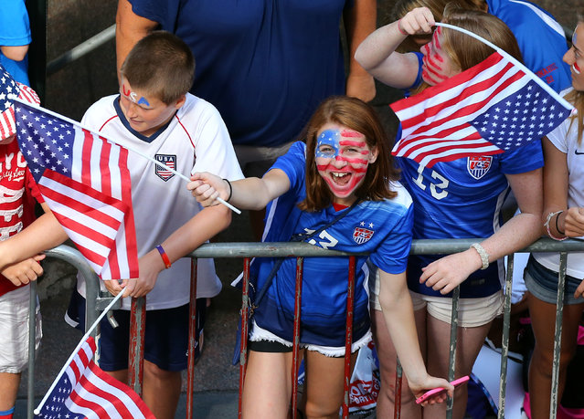 A young fan cheers while waiting for the ticker tape parade to celebrate the U.S. women's soccer team World Cup victory, Friday, July 10, 2015, in New York. (Photo by Adam Hunger/AP Photo)