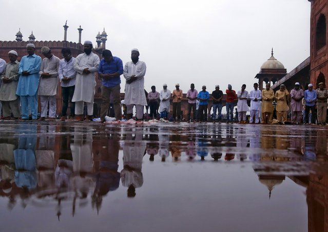 Muslims offer Friday prayers as it drizzles at the Jama Masjid (Grand Mosque) during the holy month of Ramadan in the old quarters of Delhi, India, July 10, 2015. (Photo by Anindito Mukherjee/Reuters)
