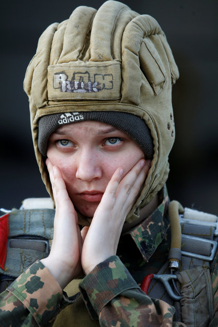 A student of the General Yermolov Cadet School reacts as she waits to board an airplane for a parachute jump at an airdrome in the village of Novomaryevskaya outside the southern city of Stavropol, Russia, May 13, 2016. (Photo by Eduard Korniyenko/Reuters)