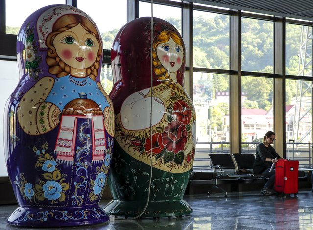 A woman sits next to giant matryoshka dolls inside a terminal of Sochi's airport in Adle, Russia, July 13, 2015. Russia will host the World Cup soccer tournament for FIFA in 2018. (Photo by Maxim Shemetov/Reuters)