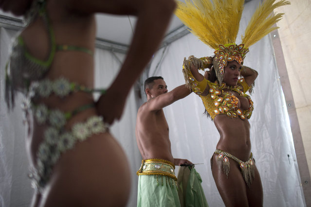 "Samba dancer Diana Prado, right, is with her costume as she prepares for a carnival parade at central station in Rio de Janeiro, Brazil, Saturday, February 2, 2013. Though samba dancers, or ""passistas"", as they're known in Portuguese, are unquestionably the star attractions of the world's most iconic Carnival celebrations, they're not on the payroll of the samba school they represent. (Photo by Felipe Dana/AP Photo)"