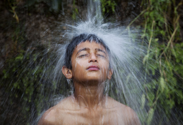 A Pakistani boy stands under an opened water line to beat the heat in Islamabad, Pakistan, Wednesday, May 7, 2014, where temperatures reached 36 degrees Celsius (97 degrees Fahrenheit). (Photo by B. K. Bangash/AP Photo)