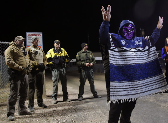 "A man in an alien mask stands at an entrance to the Nevada Test and Training Range near Area 51 September 20, 2019, outside of Rachel, Nev. People gathered at the gate inspired by the ""Storm Area 51"" internet hoax.  (Photo by John Locher/AP Photo)"