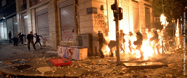 Demonstrators throw pfire bombs to riot police during violent protests in central Athens