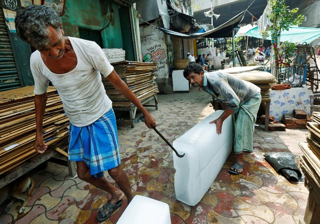 Men unload blocks of ice from a tricycle at a local market in Kolkata, India May 24, 2016. (Photo by Rupak De Chowdhuri/Reuters)