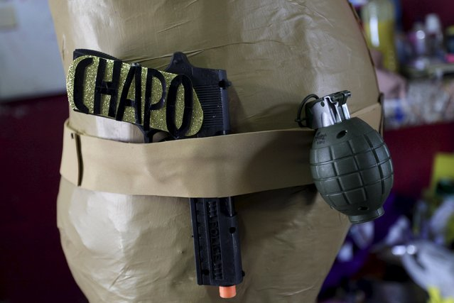 "A toy gun with the word, ""Chapo"" is seen next to a toy grenade attached to a pinata depicting the drug lord Joaquin """"El Chapo"" Guzman at a workshop in Reynosa, July 21, 2015. (Photo by Daniel Becerril/Reuters)"