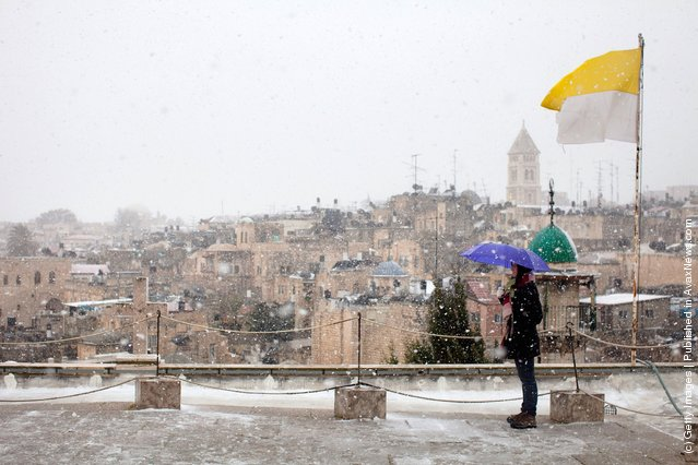 A woman stands on a rooftop as snow falls on March 2, 2012 in Jerusalem, Israel