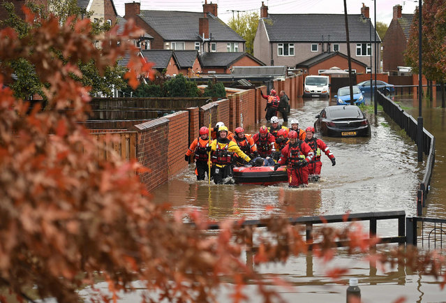 Members of the Fire and Rescue service evacuate a man by boat from a flooded house in Doncaster, northern England on November 8, 2019, following flash flooding the previous day. Over a month's worth of rain fell on parts of England Thursday, with some people forced to evacuate their homes, and others left stranded in a Sheffield shopping centre. (Photo by Oli Scarff/AFP Photo)