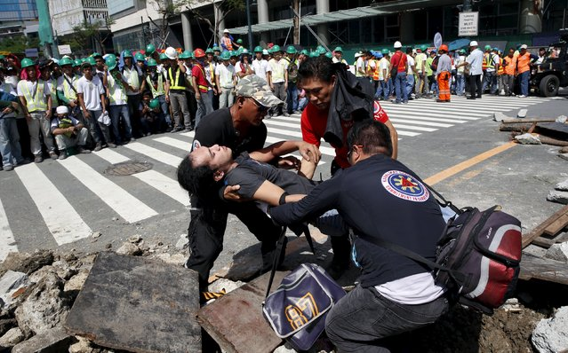 Employees carry a mock victim who was trapped in a simulated rubble during an earthquake drill in Taguig, Metro Manila in the Philippines July 23, 2015. (Photo by Erik De Castro/Reuters)