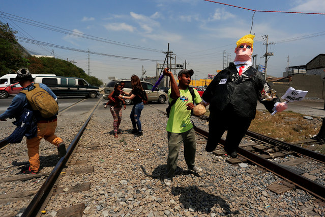 A Central American migrant hits a pinata representing U.S. President Donald Trump during a protest to raise awareness of the migrant crossing between Mexico and the U.S., on the outskirts of Monterrey, Mexico May 27, 2017. (Photo by Daniel Becerril/Reuters)