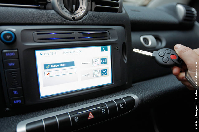 A car2go empoloyee demonstrates how the car's key is stored in the dashboard