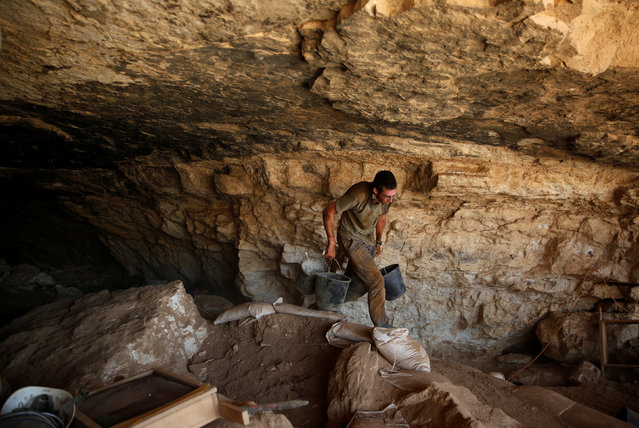 A volunteer with the Israeli Antique Authority works in the Cave of the Skulls, an excavation site in the Judean Desert near the Dead Sea, Israel June 1, 2016. (Photo by Ronen Zvulun/Reuters)