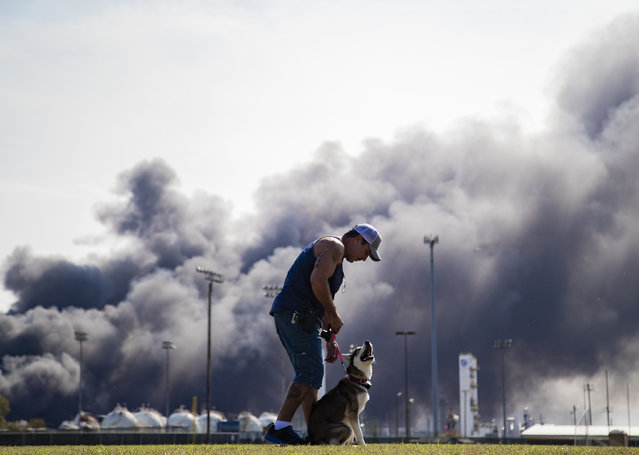 Ray Moore trains his dog Aries with a cloud of smoke in the background from the TPC Group Port Neches Operations explosion on Wednesday, November 27, 2019, in Port Neches, Texas. Multiple workers were injured early Wednesday in a massive explosion at a Texas chemical plant that also blew out the windows and doors of nearby homes. (Photo by Marie D. De Jesús/Houston Chronicle via AP Photo)