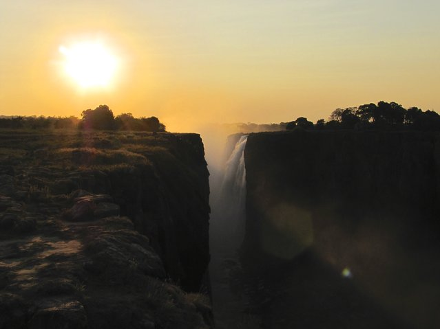 """Sunset at Victoria Falls"". As I walked along the trail thinking how perfect it was to have the sun behind me for my pictures of Victoria Falls, you can imagine my surprise when I turned around to exit the park before darkness arrived. The sun illuminated the falls from behind highlighting the blackness of the canyon where the falls were spilling into. Photo location: Victoria Falls, Zimbabwe, Africa. (Photo and caption by Thomas Burke/National Geographic Photo Contest)"