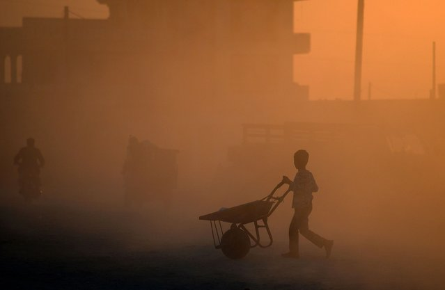 An Afghan youth pushes a wheelbarrow during sunset in Mazar-i-Sharif on April 22, 2014. Afghanistan remains at war, with civilians among the hardest hit as the Taliban wage an increasingly bloody insurgency against the government. (Photo by Farshad Usyan/AFP Photo)