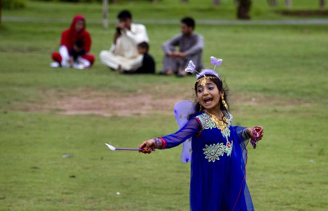 A Pakistani girl in new clothes calls to her friend while visiting a park to celebrate the Eid al-Fitr holidays in Rawalpindi, Pakistan, Saturday, July 18, 2015. (Photo by Anjum Naveed/AP Photo)