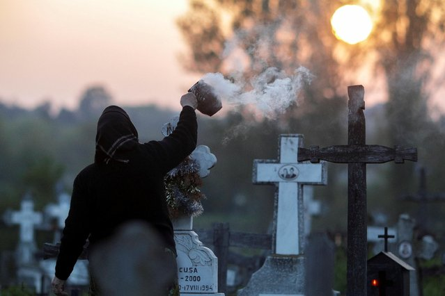 A woman burns incense near the grave of departed relatives in a cemetery south west of Romanian capital Bucharest, in the early hours of Maundy Thursday, in Copaciu, Romania, April 25, 2019. (Photo by Octav Ganea/Inquam Photos via Reuters)
