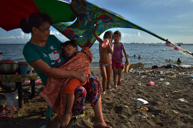 A family enjoying a makeshift beach that was used be a garbage dump near Manila bay on April 25, 2017 in Manila, Philippines. Metro Manila has been facing an increasing amount of floods due to overuse of groundwater causing the city to sink, as well as rapid rise in sea levels which has been over double the global average. The Philippines has been among the top five countries vulnerable to climate change over recent years while reports state coastal areas including parts of Manila are already below sea level causing further devastation during natural disasters, such as Typhoon Haiyan which killed thousands of people and made millions homeless in 2013. In Manila, slum dwellers face an increasing amount of threat living along the coast as floods and storms have been exacerbated flooding while there is little the residents can do except relocate to higher ground. (Photo by Jes Aznar/Getty Images)