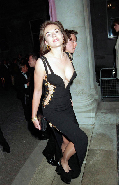 "Actress Elizabeth Hurley wears a Giani Versace dress to the premiere of ""Four Weddings and A Funeral"" held in Leicester Square on March 09, 1994 in London, England. (Photo by Dave Benett/Hulton Archive/Getty Images)"