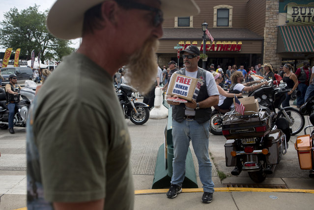 An unidentified man hands out bibles while participating in the annual Sturgis Motorcycle Rally in Sturgis, South Dakota, August 4, 2015. (Photo by Kristina Barker/Reuters)