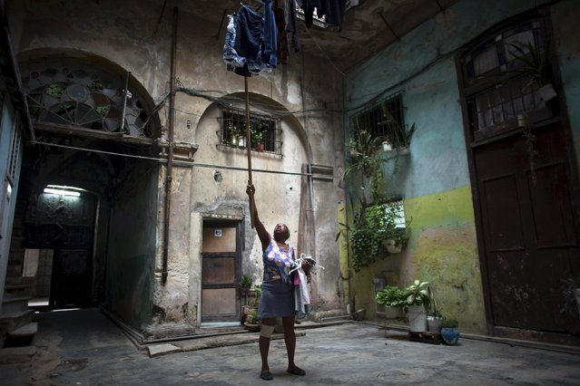 Odelia Pedroso, 59, hangs clothes at the courtyard of her home in downtown Havana, Cuba July 30, 2015. (Photo by Alexandre Meneghini/Reuters)