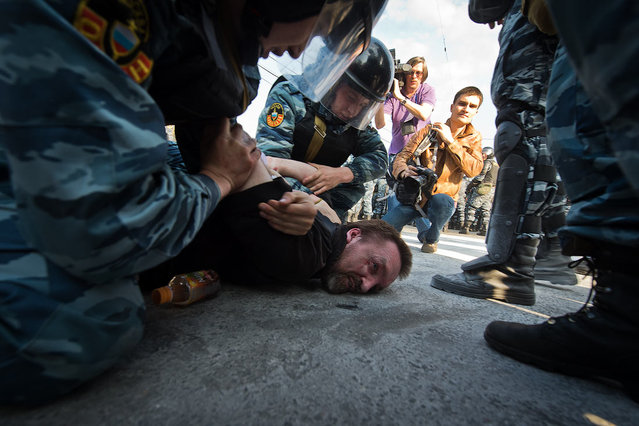 Riot police hauled away dozens of protesters and at least two opposition leaders on Sunday after scuffles broke out at a demonstration against Vladimir Putin's return to Russia's presidency, witnesses said
