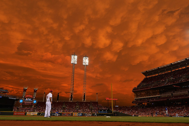 Storm clouds blanket the sky over Great American Ball Park as Starlin Castro #13 of the Chicago Cubs fields a ground ball in the fifth inning against the Cincinnati Reds as on July 7, 2014 in Cincinnati, Ohio. Cincinnati defeated Chicago 9-3. (Photo by Jamie Sabau/Getty Images)