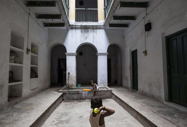 Children of Mukti Bhavan employees play cricket inside its premises in Varanasi, in the northern Indian state of Uttar Pradesh, June 17, 2014. (Photo by Danish Siddiqui/Reuters)