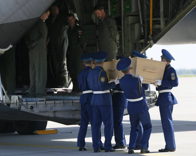 Honour guards load a coffin of one of the victims of Malaysia Airlines MH17 downed over rebel-held territory in eastern Ukraine on to a transport plane heading to the Netherlands at Kharkiv airport July 23, 2014. (Photo by Gleb Garanich/Reuters)