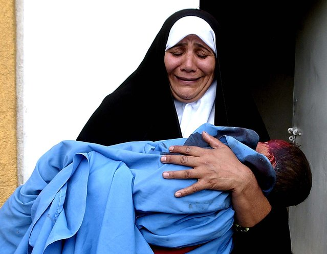 A woman holds the lifeless body of her two-year-old grandson outside Baqouba's hospital, 35 miles northeast of Baghdad, Oct. 31 2006