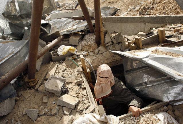 A masked Palestinian surveys a destroyed smuggling tunnel near the Gaza-Egypt border in the southern Gaza Strip January 28, 2009. (Photo by Ibraheem Abu Mustafa/Reuters)