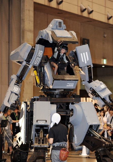 """Female """"pilot"""" Anna (C) climbs out the cockpit of Japanese electronics company Suidobashi Heavy Industry's newly unveiled robot """"Kuratas"""" at the Wonder Festival in Chiba, suburban Tokyo on July 29, 2012. The Kuratas robot, which will go on sale with a price tag of one million USD, measures four meters in height, weighs four tons and has four wheeled legs that can either be controlled remotely through the 3G network or by a human seated within the cockpit."""