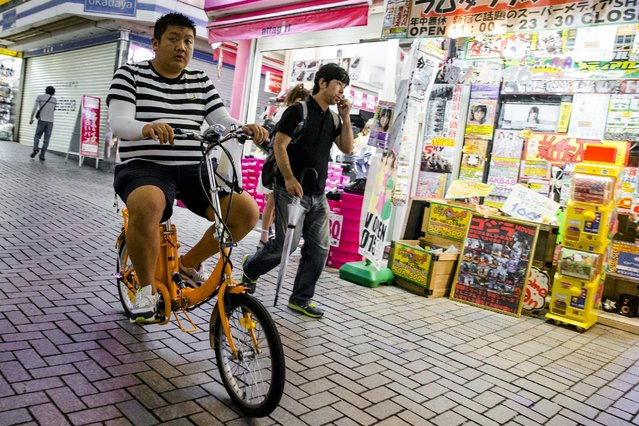 A man rides a bike in Shinjuku's nightlife district of Kabukicho in Tokyo, August 27, 2015. (Photo by Thomas Peter/Reuters)