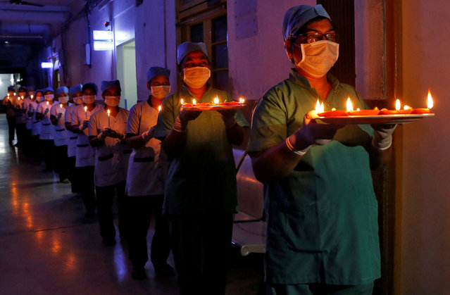 Staff members of a hospital carry candles and oil lamps to show solidarity with people who are affected by the coronavirus disease (COVID-19), and with doctors, nurses and other healthcare workers from all over the world during a 21-day nationwide lockdown to slow the spreading of the disease, in Kolkata, India, April 5, 2020. (Photo by Rupak De Chowdhuri/Reuters)